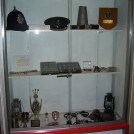Photo:Exhibit in cell No.3 - Including Brighton constables helmet, superintendants cap, loud hailer, old Sussex buttons and badges, darts cup, and old paraffin lamps.