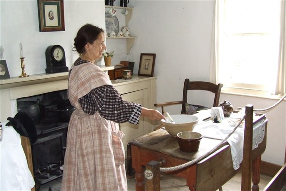 Photo:Interior of the left cottage with a cookery demonstration taking place
