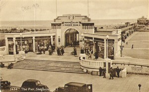 Photo:To Mum, This is a view postcard of the pier at Skeggy. It is at the end of Scarborough Ave, where my Billet is. You see the tobbaconist on the left with Players in the window? Well that is our hairdressers now! We do a lot of our drilling on the bit of pavement shown. We will have to do a guard on the pier shortly.